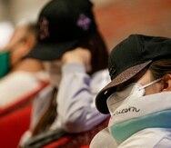 Una mujer duerme con mascarilla y tapando su rostro en el aeropuerto Changi de Singapur.