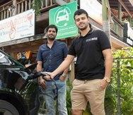 Los hermanos Leonardo y Jumil Cabán cargan un automóvil eléctrico en la estación a las afueras del restaurante Buena Vibra, en Cabo Rojo.