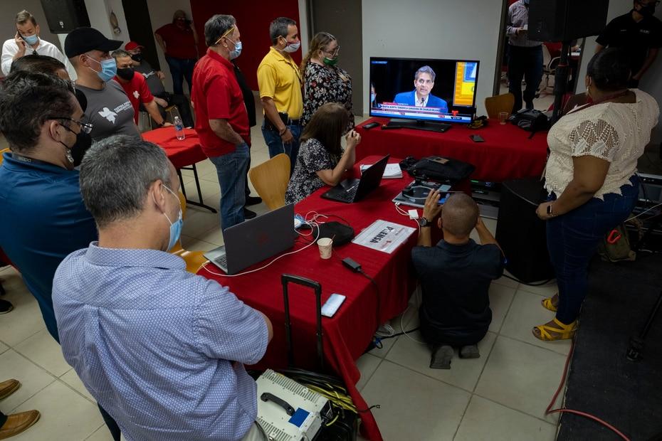 Periodistas y funcionarios del PPD observan en un televisor en la sede del partido el momento que Eduardo Bhatia acepta su derrota.