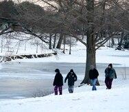 La gente camina a lo largo del borde mirando el lago congelado en Cottonwood Park en Richardson, Texas.