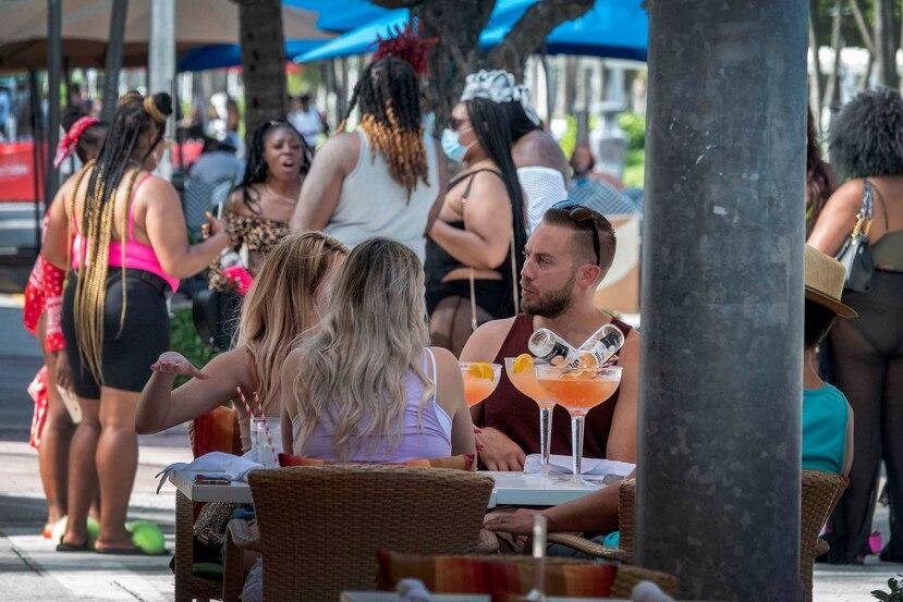 Varias personas compartiendo al aire libre en Miami Beach. (EFE)