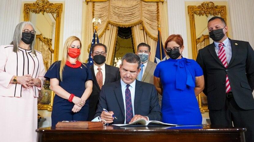 El gobernador Pedro Pierluisi estampa su firma para convertir en ley la Alerta Ashanti, rodeado de líderes legislativos.