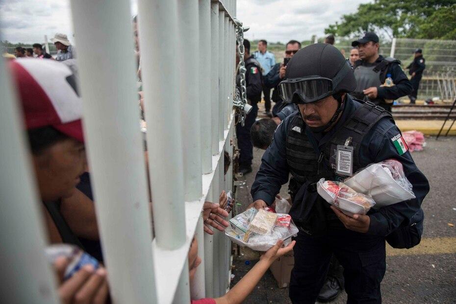 Un agente mexicano da comida a hondureños que están atrapados en un puente sin poder cruzar.