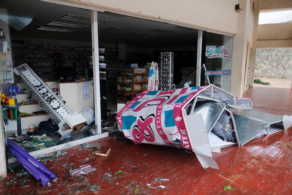 El letrero de una tienda en Cancún quedó enredado y destrozó la entrada principal al caer.