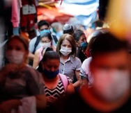 """Shoppers, wearing protective face masks as a precaution against the spread of the new coronavirus, fill a local market in Asuncion, Paraguay, Tuesday, May 5, 2020. The government authorized the reopening of some businesses under a plan coined, """"intelligent quarantine"""". (AP Photo/Jorge Saenz)"""