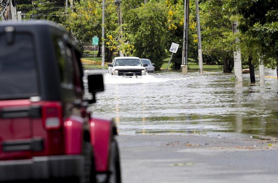 Otras personas se aventuraron a pasar en sus vehículos por la inundación.